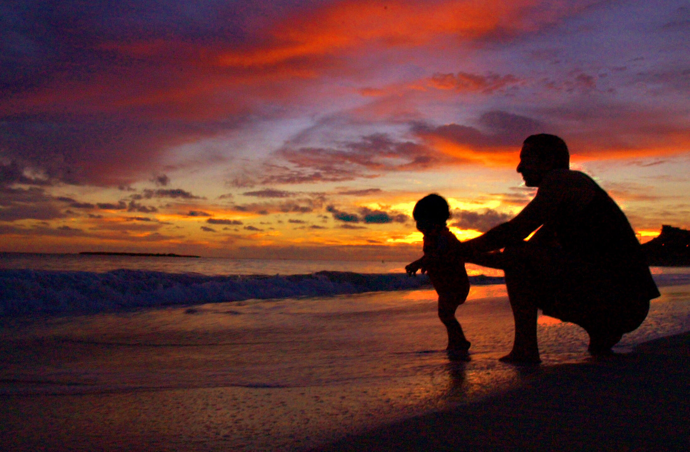 Mark Hines of Kailua plays with his son Ka'io Hines, 1, during sunrise at Kailua Beach in Kailua, Hawaii, October 19, 2003 in Kailua on the island of Oahu. Hines, a teacher in Honolulu said he wanted to let his wife sleep while his younger son woke up at before dawn. Hines recently moved to Kailua from Honolulu and this was his first sunrise since his family moved to their new home within walking distance to the ocean. NO RIGHTS CLEARANCES OR PERMISSIONS ARE REQUIRED FOR THIS IMAGE REUTERS/Lucy Pemoni LP/GAC - RTR598R